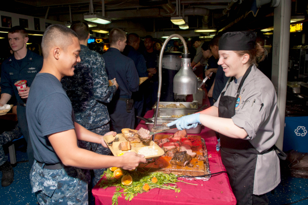 130818-N-LP801-002 U.S. 5TH FLEET AREA OF RESPONSIBILITY (Aug. 18, 2013) Culinary Specialist 3rd Class Kendra Bellinger, right, serves roast beef to Yeoman Seaman Cesar Deguzman in the mess decks aboard the aircraft carrier USS Nimitz (CVN 68). The Nimitz Carrier Strike Group is deployed to the U.S. 5th Fleet area of responsibility conducting maritime security operations, theater security cooperation efforts and support missions for Operation Enduring Freedom. (U.S. Navy photo by Mass Communication Specialist 3rd Class Raul Moreno Jr./Released)